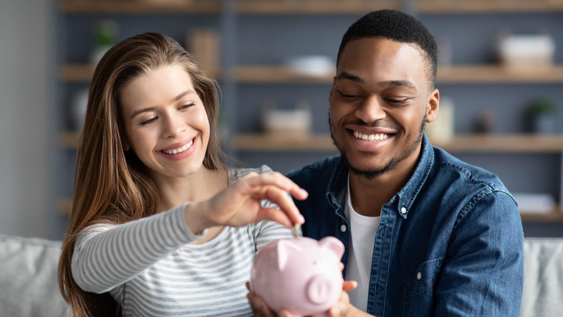 Ein Paar wirft Geld in eine Sparbüchse